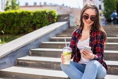 kvinna med ett limonadekoppsammanträde på trappan och texten på hennes smartphone Fotografering för Bildbyråer