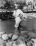 Kvinna med ett metspöanseende i vattnet (alla visade personer inte är längre uppehälle, och inget gods finns Leverantörberättigan arkivfoton