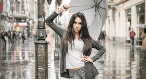 Kvinna med ett paraply under regn på en stadsgata Arkivfoton