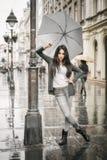 Kvinna med ett paraply under regn på en stadsgata Royaltyfria Bilder