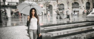 Kvinna med ett paraply under regn på en stadsgata Arkivfoto