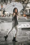 Kvinna med ett paraply under regn på en stadsgata Arkivbilder