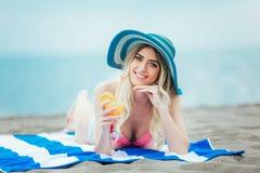 Kvinna med exponeringsglas av coctailen i handen som ligger på sandstranden arkivfoton