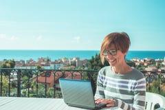 Kvinna med exponeringsglas och tillfälliga kläder som utomhus arbetar på bärbara datorn på terrass Härlig bakgrund av gröna kulla royaltyfria bilder
