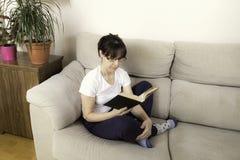 Kvinna med exponeringsglas som läser en bok på en soffa royaltyfri foto
