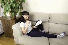 Kvinna med exponeringsglas som läser en bok på en soffa royaltyfri fotografi