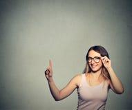 Kvinna med exponeringsglas som pekar upp med fingret på tomt kopieringsutrymme Royaltyfria Bilder