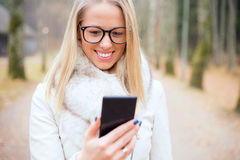 Kvinna med exponeringsglas som ser smartphonen Royaltyfri Foto