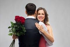 Kvinna med förlovningsringen och rosor som kramar mannen royaltyfria bilder