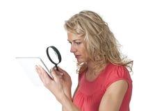 Kvinna med förstoringsglas- och minnestavlaPC Royaltyfria Foton