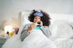 Kvinna med feber genom att använda termometern och kalla doktor By Phone Royaltyfri Foto
