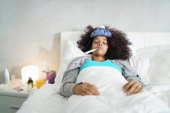 Kvinna med feber genom att använda termometern och vila i säng Arkivbild