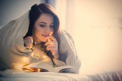 Kvinna med felika ljus och boken Royaltyfri Bild