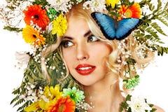 Kvinna med fjärilen och blomman. Arkivbild