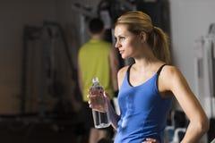 Kvinna med flaskan av vatten som bort ser på idrottshallen Royaltyfri Foto