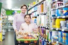 Kvinna med flickan som söker efter mat i supermarket Arkivbilder