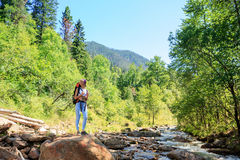 Kvinna med floden för ryggsäckloppberg royaltyfria foton