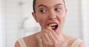 Kvinna med flosslokalvårdtänder på badrummet arkivfilmer