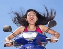 Kvinna med flyghår som rider en moped arkivbilder