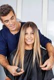 Kvinna med frisören Measuring Her Hair på salongen Arkivbilder