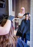 Kvinna med frisören som in ser prövkopian för hårfärg Royaltyfri Fotografi
