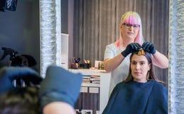 Kvinna med frisören som ser prövkopian för hårfärg i spegel Royaltyfri Foto