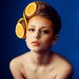 Kvinna med frukt i hår royaltyfria bilder
