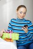 Kvinna med gåvaasken genom att använda smartphonen arkivfoto