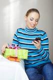Kvinna med gåvaasken genom att använda smartphonen arkivbild