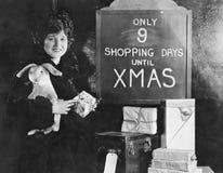 Kvinna med gåvor och tecken med nummer av shoppingdagar tills jul (alla visade personer inte är längre uppehälle och inget gods Fotografering för Bildbyråer