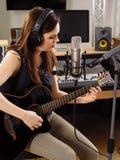 Kvinna med gitarren i en inspelningstudio Royaltyfri Foto