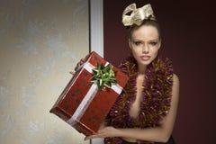 Kvinna med glitter och julgit Royaltyfria Bilder