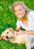 Kvinna med golden retriever som ligger på gräset royaltyfria bilder