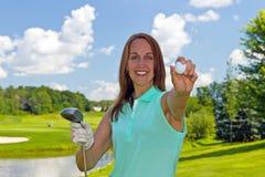 Kvinna med golfboll och klubban på farleden Fotografering för Bildbyråer