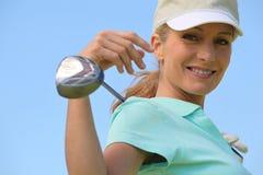 Kvinna med golfklubben Royaltyfri Bild