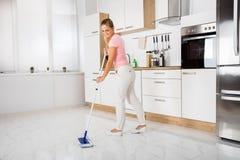Kvinna med golvmoppanseende i köket fotografering för bildbyråer