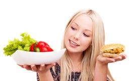 Kvinna med grönsaker och hamburgaren Fotografering för Bildbyråer