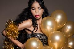 Kvinna med guld- ballonger Arkivbild