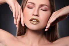 Kvinna med guld- läppstift på grå bakgrund royaltyfria bilder
