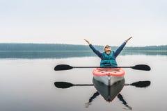 Kvinna med händer som upp tycker om extremt lugn av sjön från arkivfoton