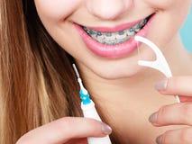 Kvinna med hänglsen som gör ren tänder med tandborsten arkivbild