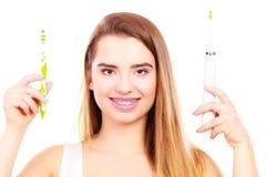 Kvinna med hänglsen som rymmer den elektriska och traditionella tandborsten Arkivfoto