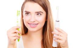 Kvinna med hänglsen som rymmer den elektriska och traditionella tandborsten Royaltyfri Foto