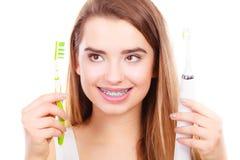 Kvinna med hänglsen som rymmer den elektriska och traditionella tandborsten Royaltyfria Foton