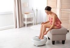 Kvinna med härliga ben genom att använda fotbadet hemma royaltyfri foto