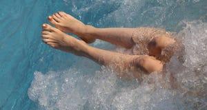 Kvinna med härliga ben i pölen med bubbelpoolen av luxuriouen arkivfoto