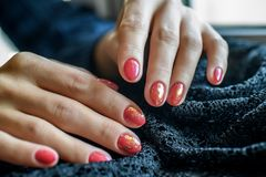 Kvinna med härliga manicured röda fingernaglar som korsar behagfullt hennes händer för att visa dem till tittaren på en grå färg Royaltyfri Foto