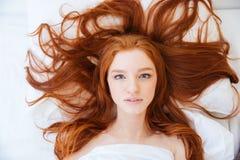Kvinna med härligt långt rött hår som ligger i säng royaltyfria foton