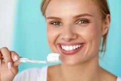 Kvinna med härligt leende som borstar sunda vita tänder Royaltyfri Foto