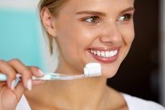Kvinna med härligt leende som borstar sunda vita tänder Arkivfoto